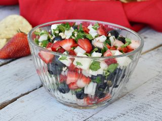 clear glass bowl with jicama salsa with strawberries and blueberries and cilantro