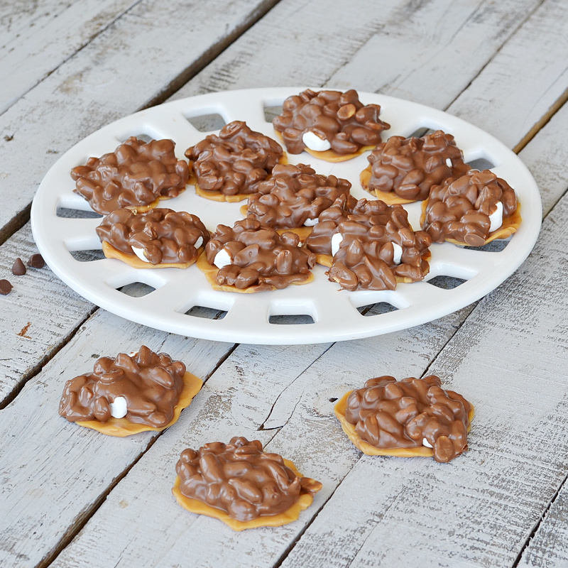 white tray with caramel peanut clusters on white wooden table