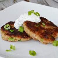 closeup of two tuna patties on a white plate with sour cream dill topping and chopped chives