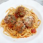 closeup of white bowl with with spaghetti and meatballs