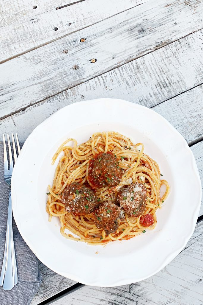 overhead shot of white bowl with with spaghetti and meatballs
