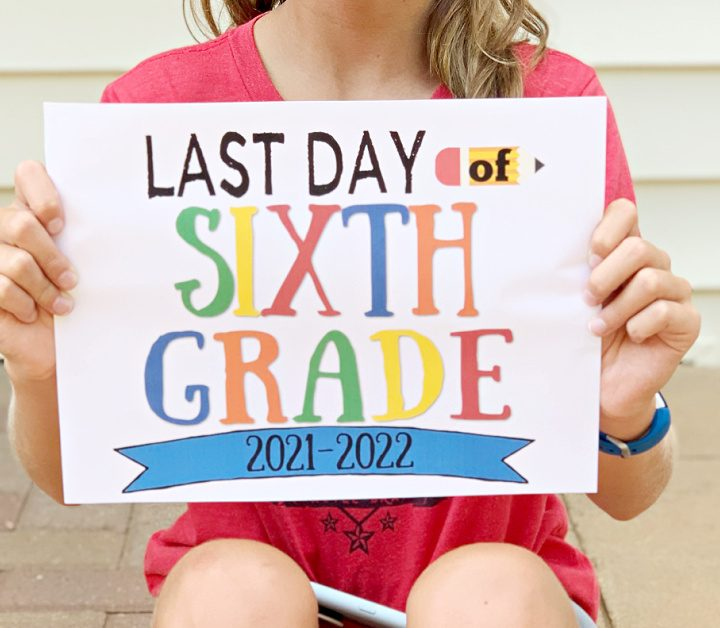 Sitting girl in red shirt holding up last day of sixth grade sign