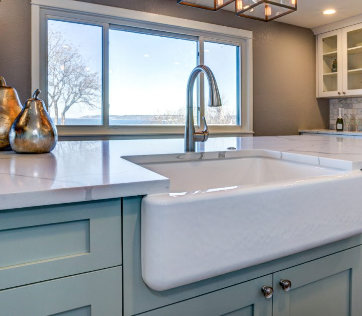 Clean kitchen counter with light blue cabinets with white sink